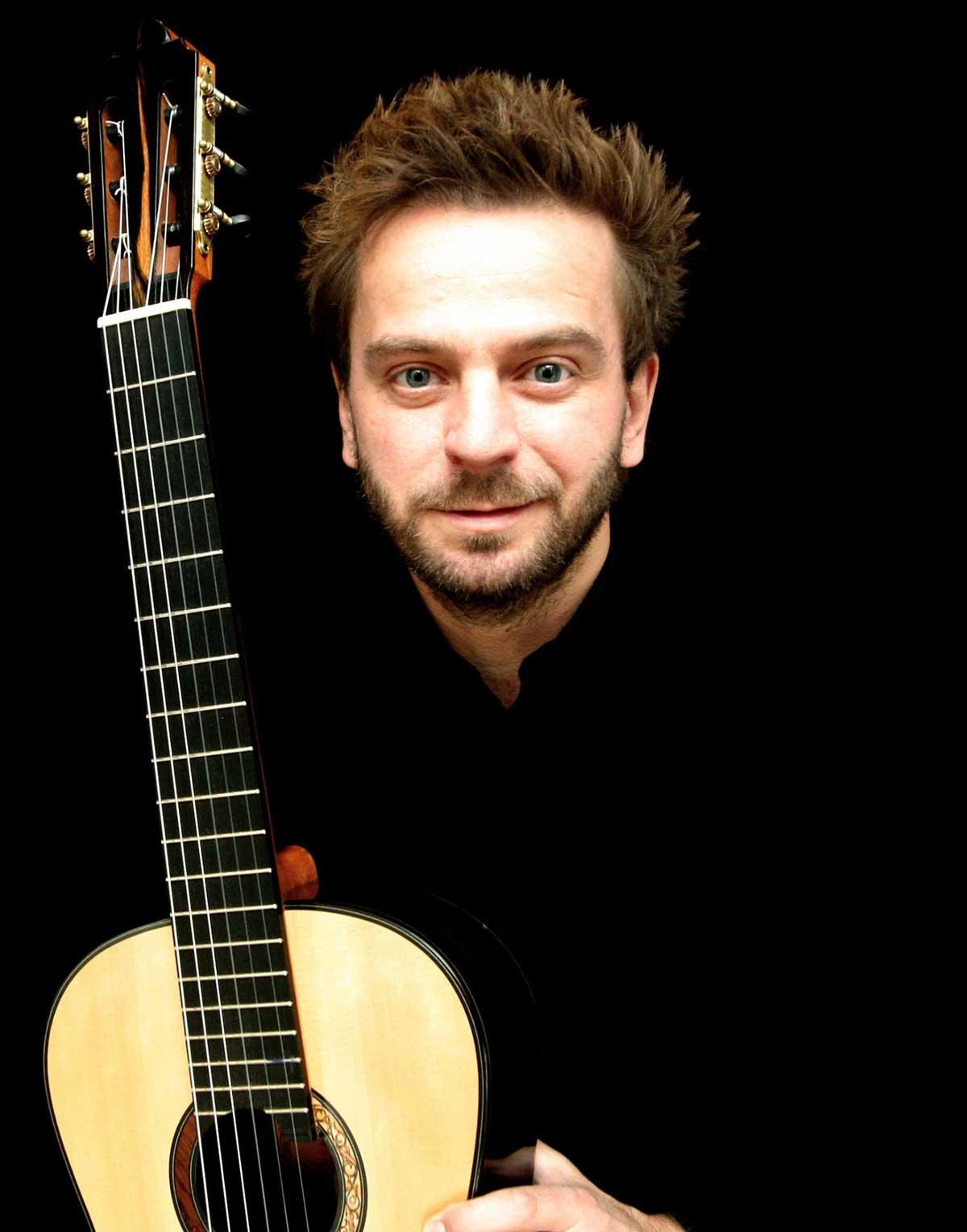 Marcin Dylla with a guitar
